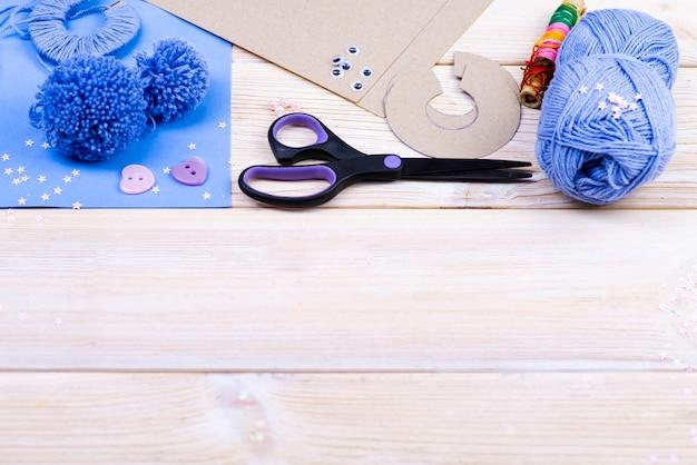 Een set voor handwerk op een houten tafel. draden, schaar, papier voor het maken van pompons
