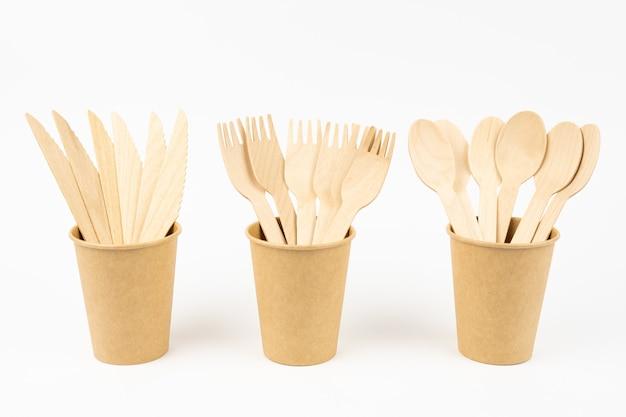 Een set wegwerpservies en houten bestek gemonteerd in wegwerpglazen