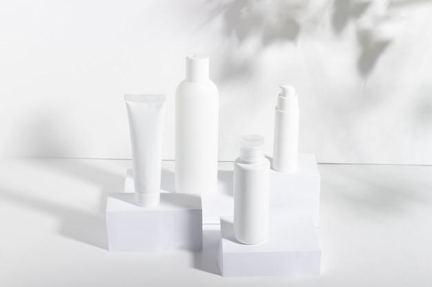 Een set witte cosmetische potten op vierkante stands met schaduwen. tandpasta, gezichts- en lichaamscrème, haarshampoo. professionele cosmetica voor huidverzorging. biologische cosmetica.