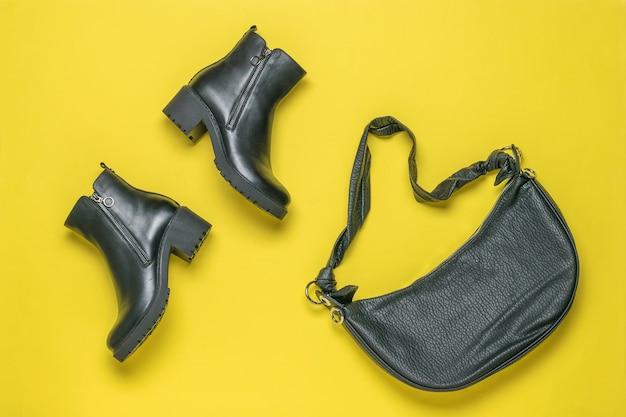 Een set zwarte enkellaarsjes voor dames en een leren tas op een gele achtergrond. plat leggen.