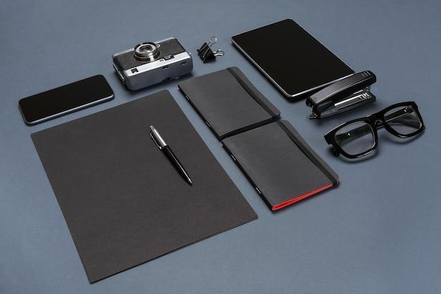 Een set zwarte kantooraccessoires, bril, oude camera en tablet op grijze achtergrond. plat leggen. stilleven. mock-up