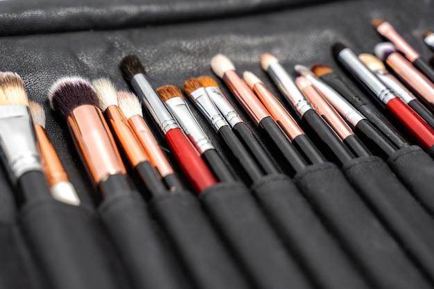 Een set zwarte make-upborstels in een zwart lederen etui.