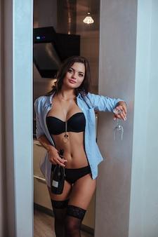 Een sexy brunette in haar ondergoed drinkt wijn alleen vrouwelijke depressie en verveling voor een man