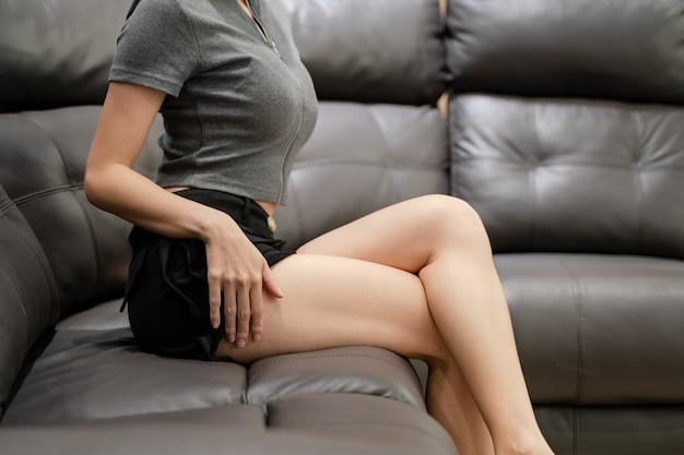 Een sexy dame zit op de zwartleren bank, haar arm geheven, benen gekruist.