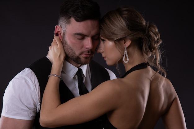 Een sexy meisje met licht haar streelt de wang van haar man sluw en gluurt naar hoeveel hij er echt van houdt