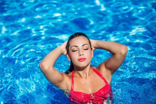 Een sexy meisje zwemt in het zwembad.
