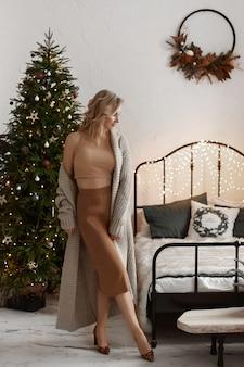 Een sexy model meisje in een gebreide rok en blouse poseren in het luxe interieur ingericht voor de c...