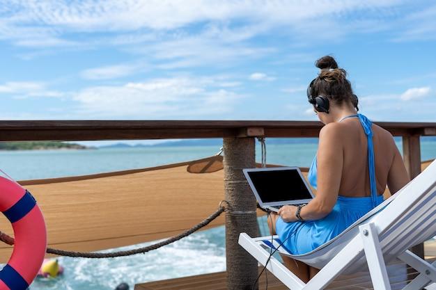 Een sexy vrouw gebruikt een laptop en draagt een koptelefoon, werkt door verbinding te maken met internet.