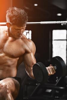 Een shirtless gespierde man doet biceps-oefeningen met halteroefeningen
