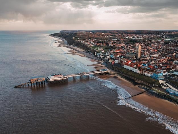 Een shot in vogelvlucht van de stad, het openbare strand en de pier op een sombere dag