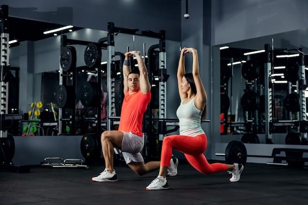 Een shot met een stel dat overeenkomt met een fitnessoutfit die zich uitstrekt en de training tot een einde brengt