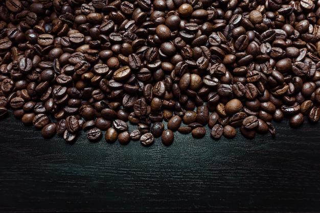Een shot van bovenaf van veel koffiebonen op een donkere houten achtergrond