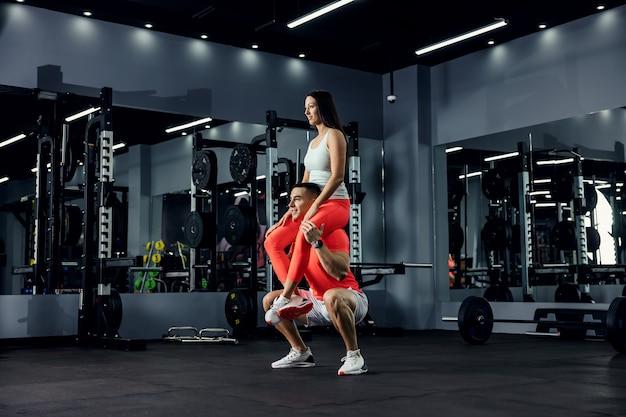 Een shot van de positieve vibratie van een fitnesspaar. de man zit gehurkt en het meisje zit op zijn schouders in een donkere sportschool. paar doel, fitnessondersteuning