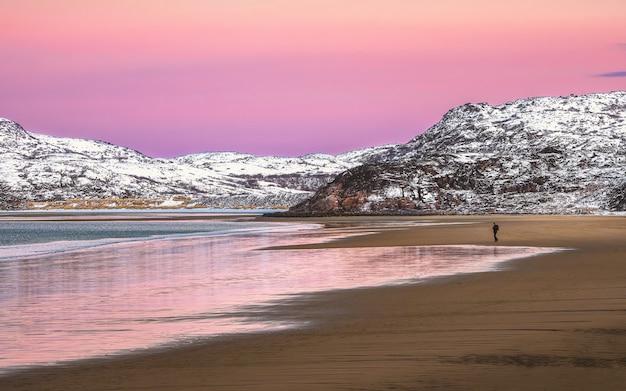 Een silhouet, een figuur op een strand. geweldig zonsopgang polair landschap met witte besneeuwde bergketen aan de horizon. panoramisch uitzicht op de noordelijke ijszee.