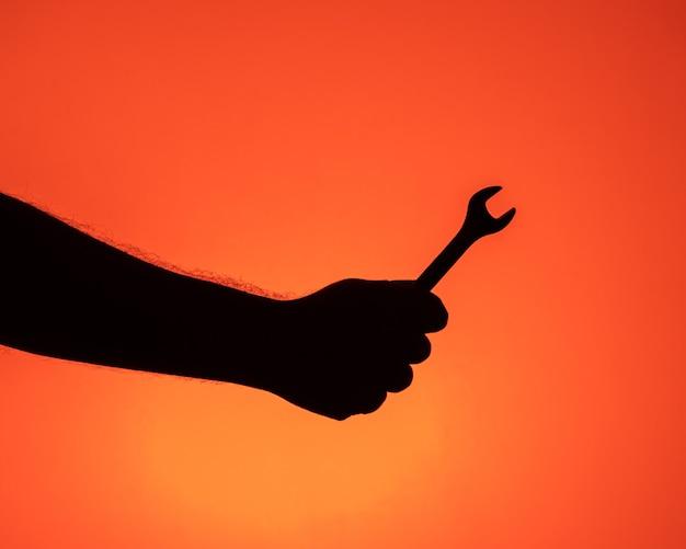 Een silhouet van een arm die een moersleutel vasthoudt.