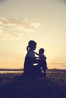 Een silhouet van een gelukkige jonge moeder harmonieuze familie buitenshuis.