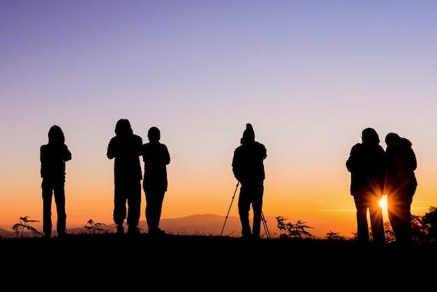 Een silhouet van een toerist die zich op een bergzonsopgang bevindt die in mae hong son, thailand fotografeert.
