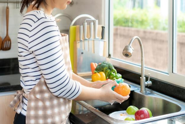 Een sinaasappel en ander fruit wassen boven de gootsteen