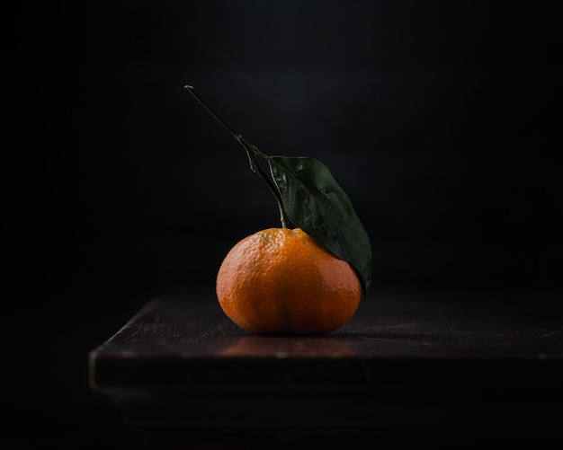 Een sinaasappel op zwarte tafel