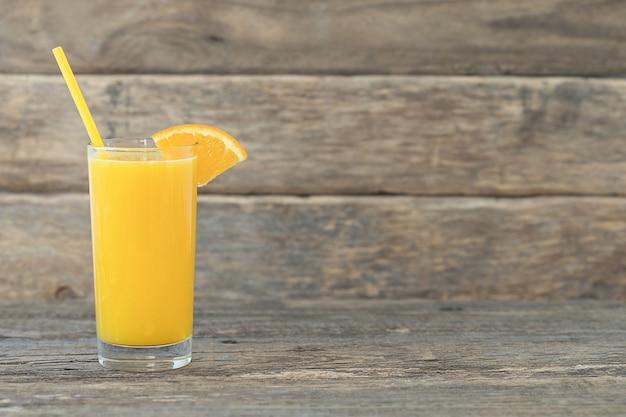 Een sinaasappelsap in een glas met stro en een schijfje sinaasappel op een houten achtergrond