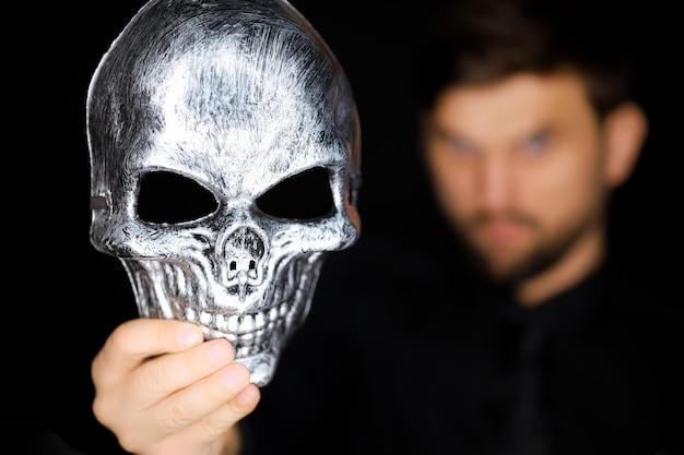 Een skeletmasker dat een man op zijn gezicht wil zetten
