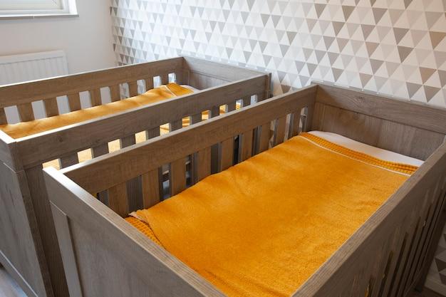 Een slaapkamer met twee eenpersoonsbedden met houten babybedjes voor broers en zussen pasgeboren baby's modern stijlvol interieur