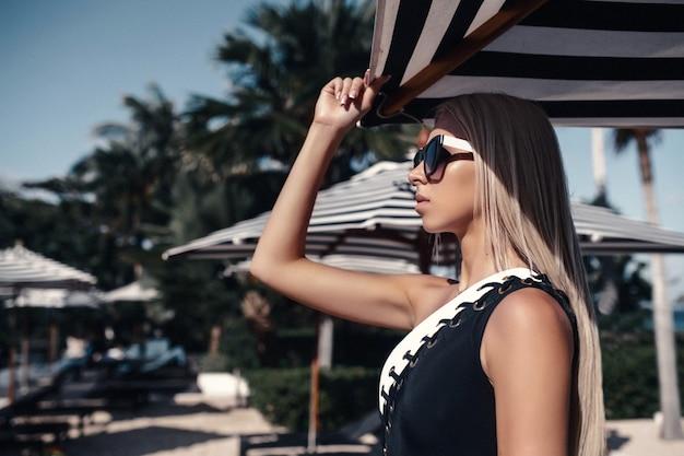 Een slank blondje dat zwart-wit zwempak draagt en strand stelt