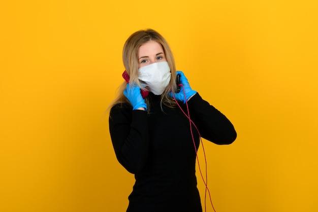 Een slank meisje in een zwarte bodysuit en medisch masker tegen virussen vormt zich
