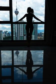 Een slank meisje kijkt door een groot raam naar de stad. hoge verdieping.