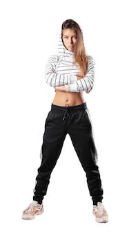 Een slank meisje met lang haar in joggingbroek en een kort gestreept sweatshirt met capuchon staat met haar armen gekruist op haar borst