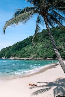 Een slank meisje rust onder een palmboom op een tropisch strand. heet klimaat
