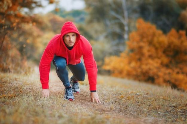 Een slanke atletische jogger-man in een zwarte legging en rode jassen met capuchon aan het begin die zich voorbereidde om te rennen