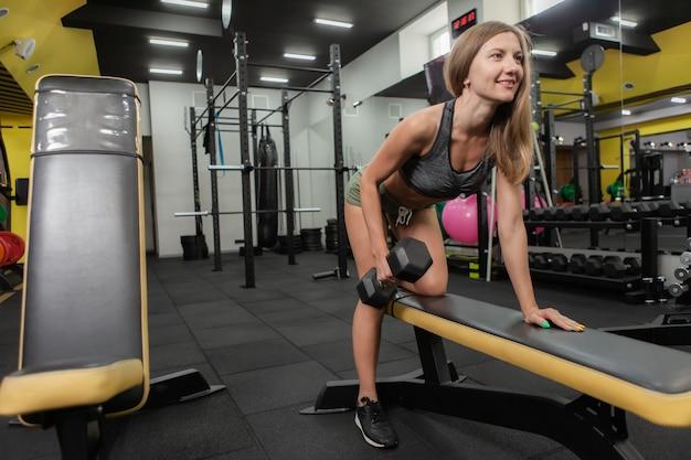 Een slanke fitte vrouw die dumbbells oefent in een helling in de sportschool. gezonde levensstijl. bodybuilding en fitness
