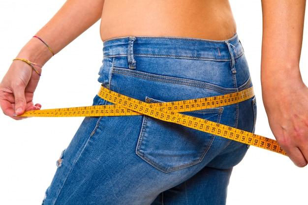 Een slanke jonge vrouw in jeans met een meetlint na een succes