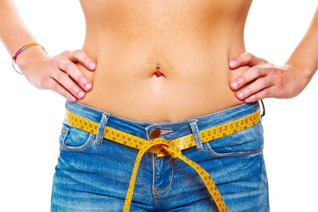 Een slanke jonge vrouw in jeans met een meetlint na een succesvol dieet