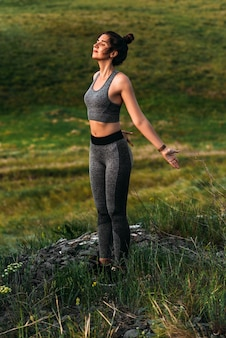 Een slanke vrouw doet yoga-oefeningen tegen een ongelooflijke achtergrond van de natuur. een vrouw doet yoga in de open lucht. gezond en yogaconcept. meisje doet gymnastiek op frisse lucht tijdens een wandeling door de natuur.