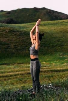 Een slanke vrouw doet yoga-oefeningen tegen een ongelooflijke achtergrond van de natuur. het meisje doet yoga in de frisse lucht. gezond en yogaconcept. meditatie en ontspanning. gezonde levensstijl. ruimte kopiëren