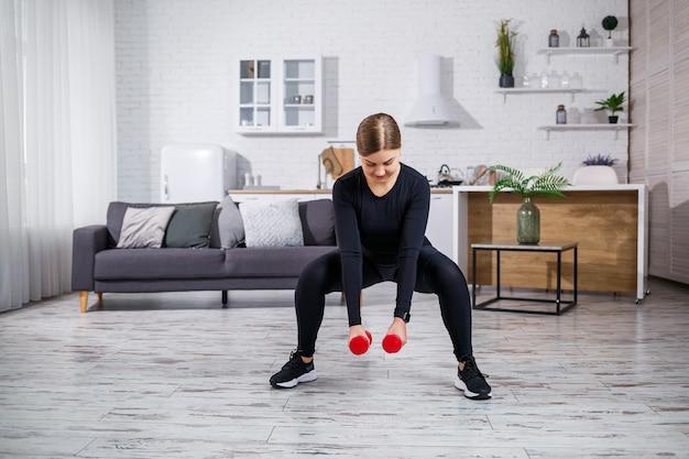 Een slanke vrouw gaat thuis sporten in een top en legging. thuis fitnessen voor een mooi lichaam. oefeningen met halters voor het vrouwelijk lichaam. squats met dumbbells voor stevige billen