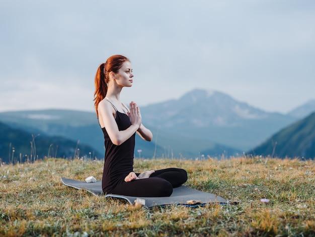 Een slanke vrouw houdt zich bezig met yoga in de natuur in de bergen in legging en een t-shirt