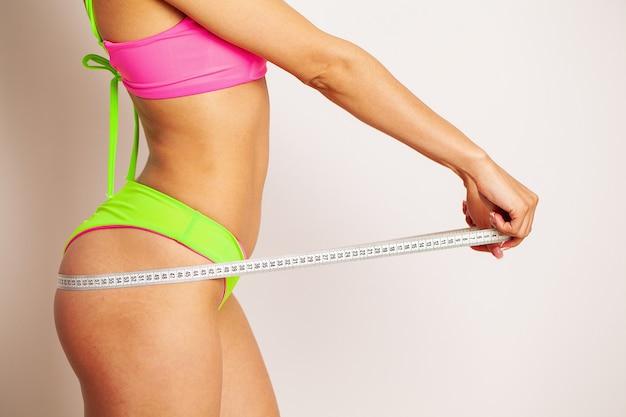 Een slanke vrouw meet de omvang van haar middel.