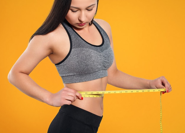 Een slanke vrouw meet haar middel met een meetlint. tegen een gele achtergrond.