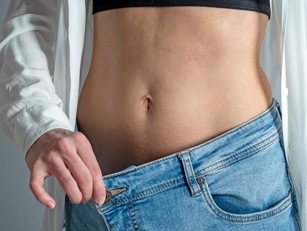 Een slanke vrouw met een blote buik laat zien hoe ze gewicht verloor, terwijl ze haar spijkerbroek met haar hand vasthield.
