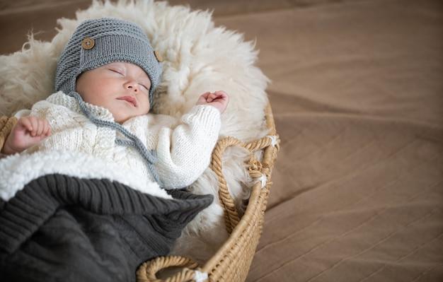 Een slapende baby in een rieten wieg in een warme gebreide muts onder een warme deken met een speeltje in het handvat.