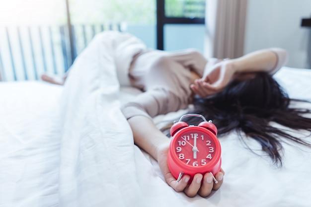 Een slaperige aziatische jonge vrouw met een wekkerzoon om wakker te worden om te slapen