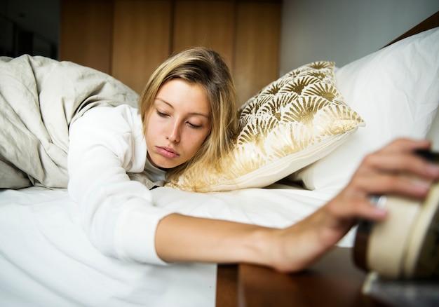 Een slaperige kaukasische vrouw die een alarm uitzet