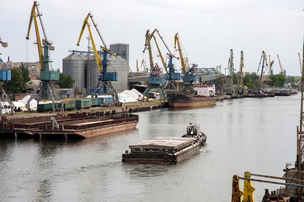 Een sleepboot trekt een schuit de rivier af tegen de achtergrond van een haven met kranen en afgemeerde schepen