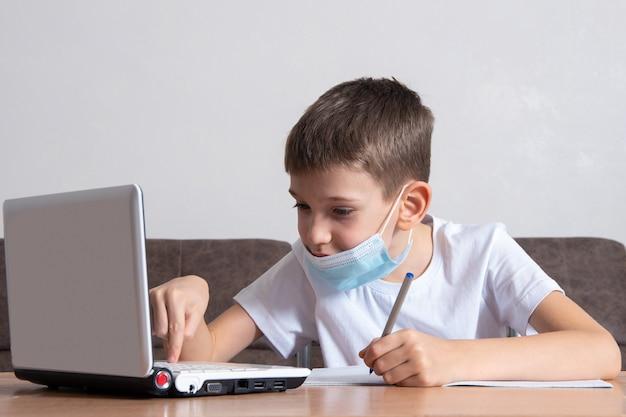 Een slimme jongen, een schooljongen, zit thuis aan een bureau, studeert online op een laptop en schrijft informatie in zijn notitieboekje. online onderwijsconcept, afstandsonderwijs