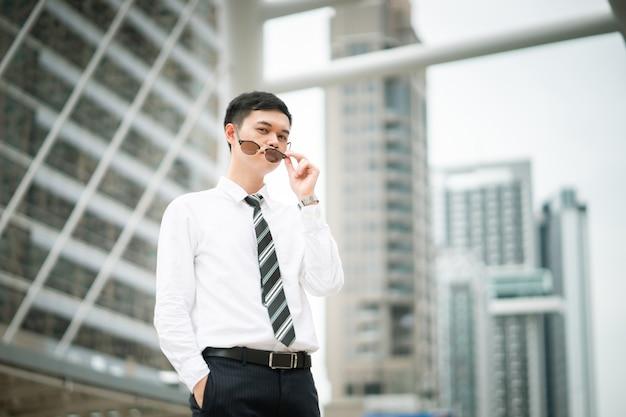 Een slimme kerel staat in de stad, hij draagt een wit overhemd en een das.