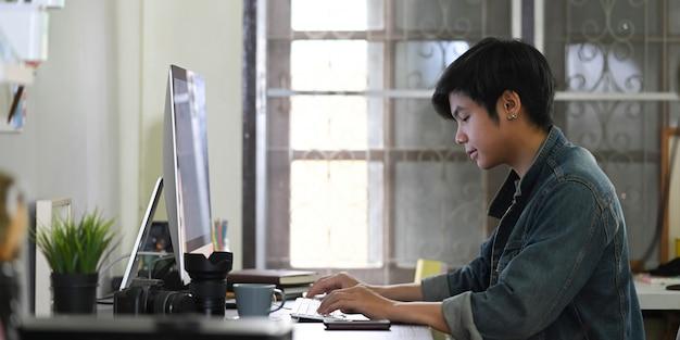 Een slimme man typt op een toetsenbord aan het bureau, omringd door fotograafapparatuur.