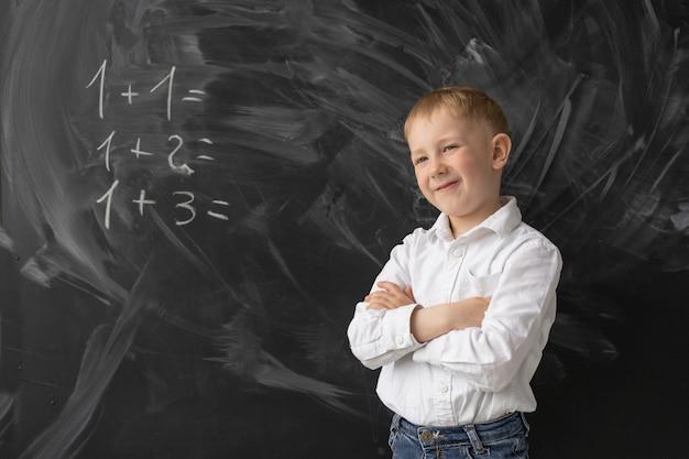 Een slimme schooljongen staat aan het bord in de klas en lacht.